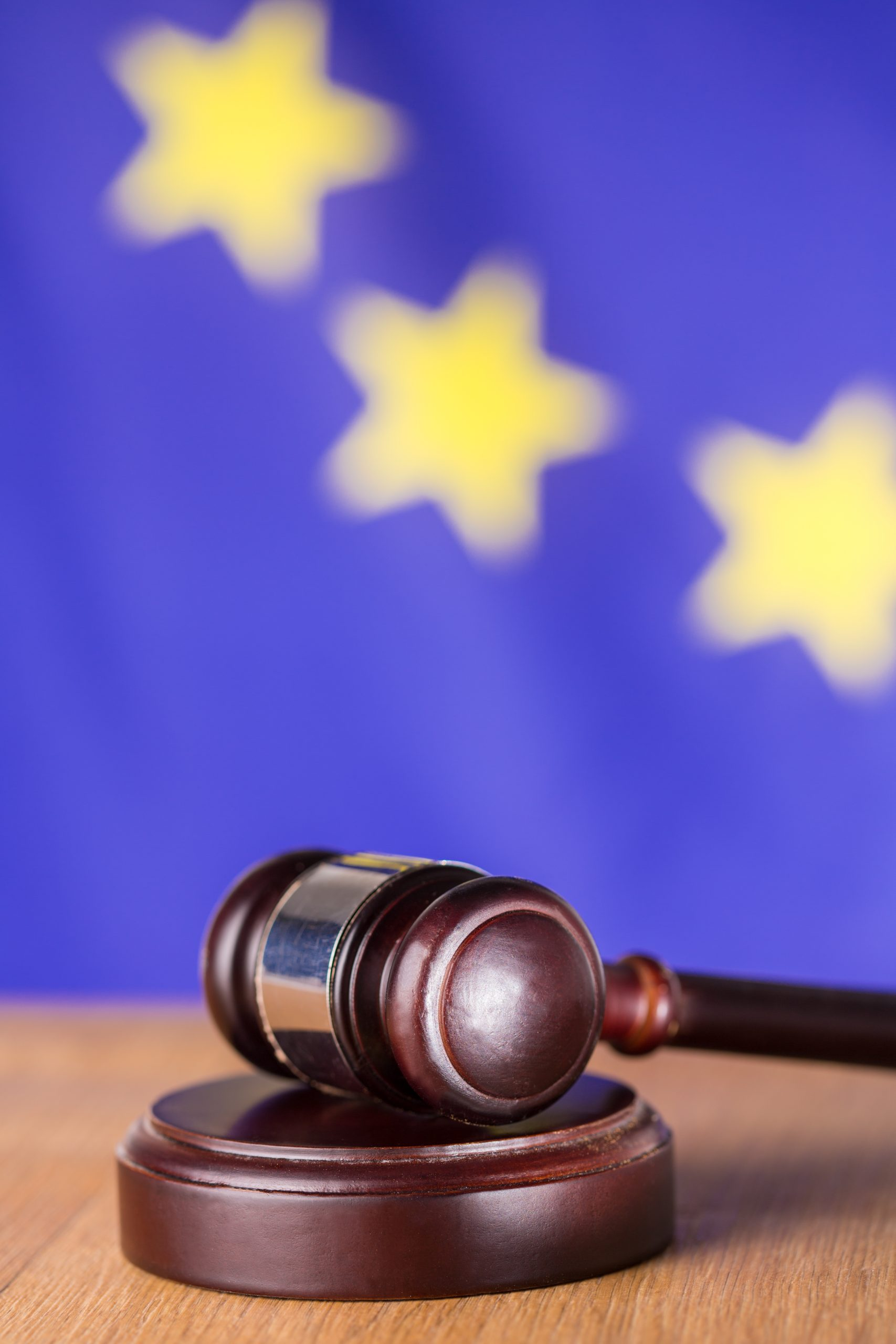 Oak gavel resting on soundblock on european union flag background